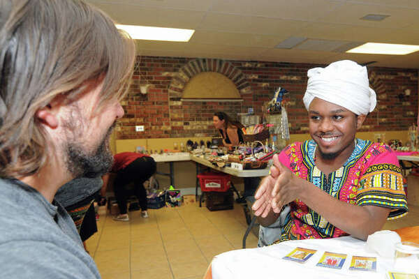 Hezekiah Williams of St. Louis does a reading for a customer at the Autumn Psychic and Crystal Fair in Alton on Sunday.