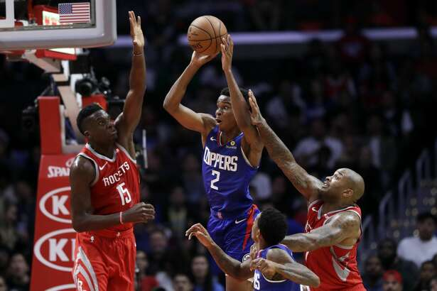 Los Angeles Clippers' Shai Gilgeous-Alexander (2) is defended by Houston Rockets' Clint Capela (15) and Eric Gordon, right, during the second half of an NBA basketball game Sunday, Oct. 21, 2018, in Los Angeles. The Clippers won, 115-112. (AP Photo/Marcio Jose Sanchez)