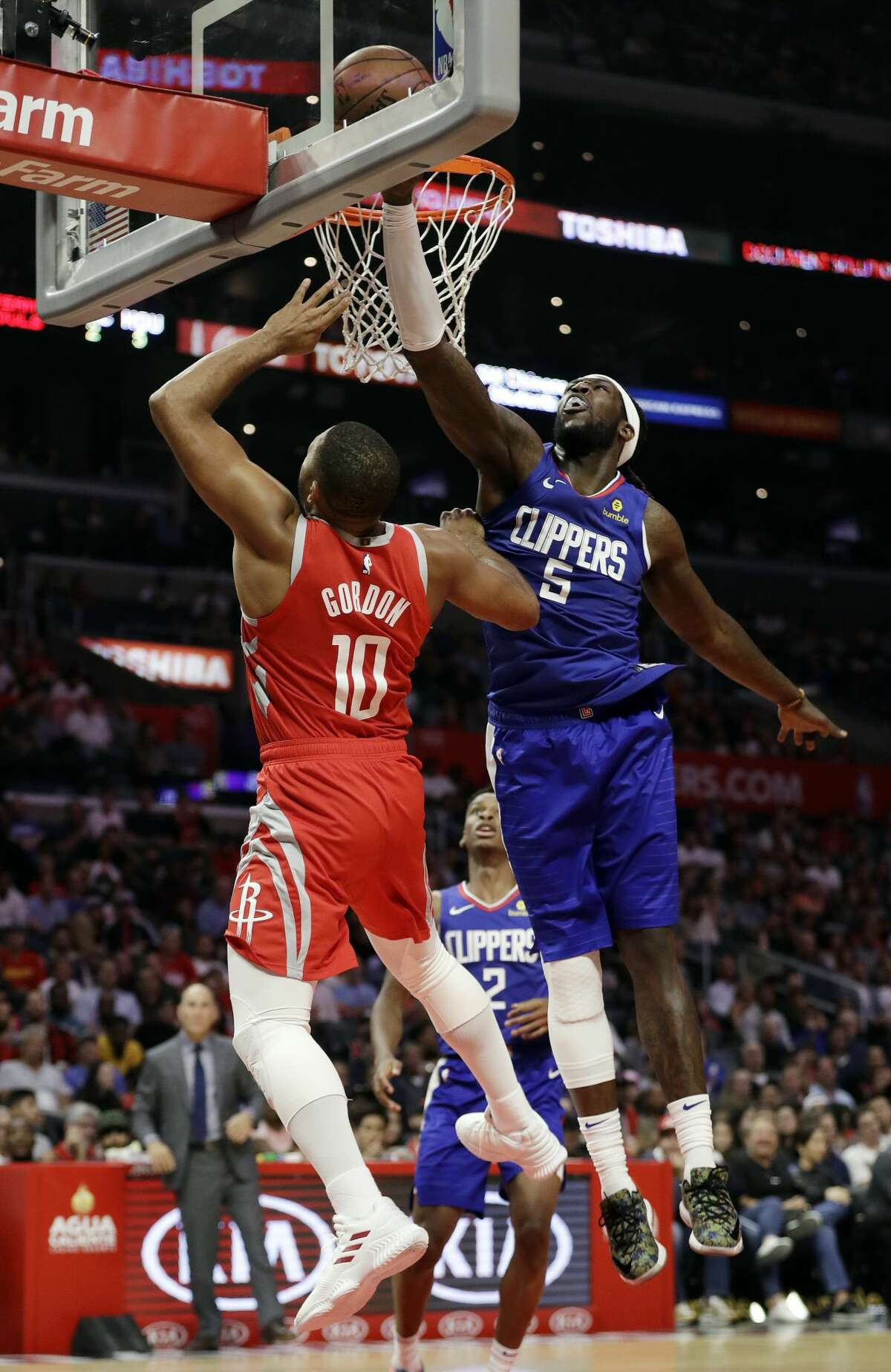 Los Angeles Clippers' Montrezl Harrell (5) blocks a shot from Houston Rockets' Eric Gordon (10) during the second half of an NBA basketball game Sunday, Oct. 21, 2018, in Los Angeles. The Clippers won, 115-112. (AP Photo/Marcio Jose Sanchez)