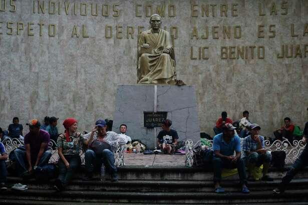 Central American migrants making their way to the U.S. in a large caravan rest under a statue of Mexico's first Indian president Benito Juarez in Tapachula, Mexico, Sunday, Oct. 21, 2018. A growing caravan of Honduran migrants streamed through southern Mexico on Sunday heading toward the United States, after making an end-run around Mexican agents who briefly blocked them at the Guatemalan border.