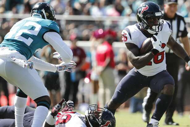 Houston Texans running back Lamar Miller (26) breaks away from Jacksonville Jaguars strong safety Barry Church (42) during the first quarter of an NFL football game at TIAA Bank Field on Sunday, Oct. 21, 2018, in Jacksonville.