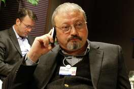 FILE - In this Jan. 29, 2011, file photo, Saudi Arabian journalist Jamal Khashoggi speaks on his cellphone at the World Economic Forum in Davos, Switzerland. In recent months, the Trump administration has repeatedly put off the release of its long-awaited Mideast peace plan. Now, the death of Saudi journalist Jamal Khashoggi at the hands of Saudi agents may put the plan into a deep freeze.