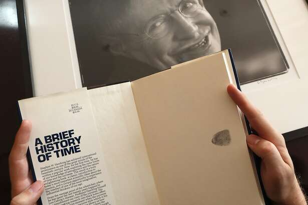 A Book, signed with a thumb print by Stephen Hawking is one of the personal and academic possessions of Stephen Hawking, photo behind, at the auction house Christies in London, Friday, Oct. 19, 2018. The online auction announced Monday Oct. 22, 2018, by auctioneer Christie's features 22 items from Hawking, including his doctoral thesis on the origins of the universe, with the sale scheduled for 31 October and 8 November. (AP Photo/Frank Augstein)
