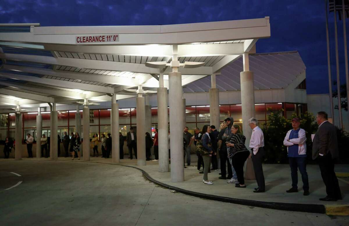 People wait in line for the West Gray early voting place to open Monday, Oct. 22, 2018, in Houston.