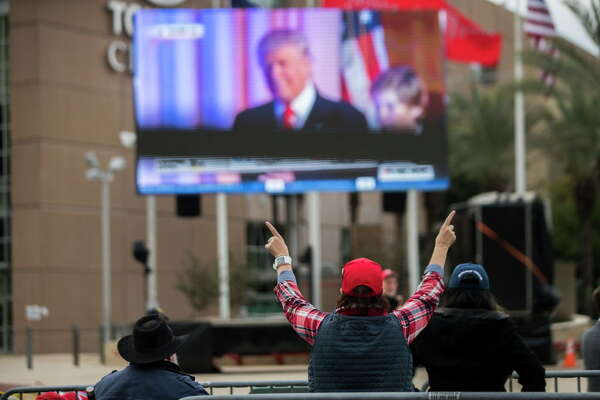 A President Donald Trump raises her arms viewing a video of the moment Trump won the presidency in 2016. The video is placed outside the Toyota Center for the supporters waiting outside for the MAGA Rally, Monday, Oct. 22, 2018, in Houston.