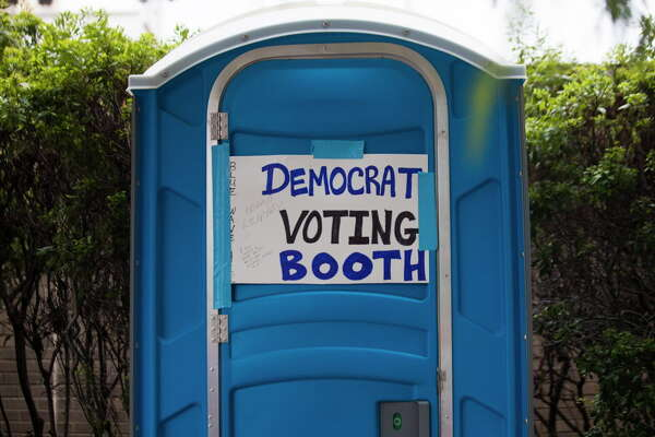 A sign is placed on front of a portable toilet outside the Toyota Center where President Donald Trump will rally his supporters in favor of Senator Ted Cruz, Monday, Oct. 22, 2018, in Houston.