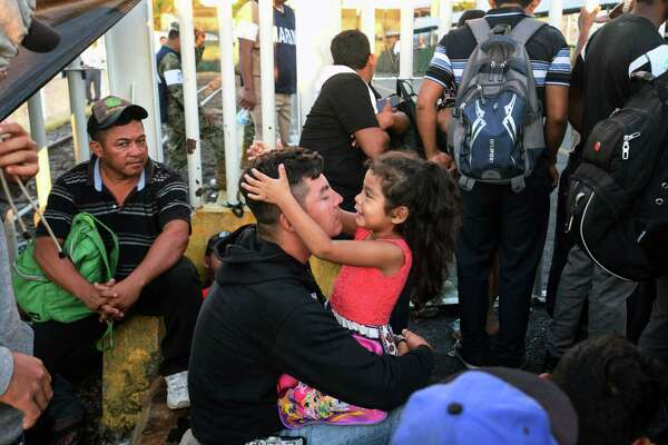 A Honduran migrant and his daughter, who are taking part in a caravan heading to the US, rest as they wait to cross the border from Ciudad Tecun Uman in Guatemala, to Ciudad Hidalgo, Mexico. President Donald Trump on Monday called the migrant caravan heading toward the US-Mexico border a national emergency, saying he has alerted the US border patrol and military.