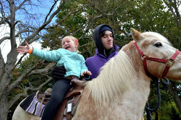 Devyn Kosowsky, 4, of Darien, has second thoughts about her first pony ride, though ably assisted by Jacob Matzinger of Pied Piper Pony Rides of Patterson, N.Y., at the 22nd annual Darien YMCA and Holly Pond School Family Fun Day, Sunday, Oct. 21, 2018, in Darien, Conn.