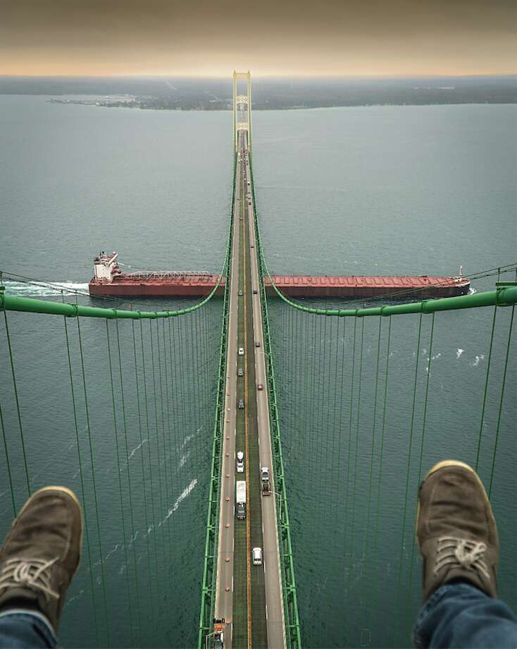 Local photographer Tyler Leipprandt dangles his feet off of the Mackinac Bridge Sunday afternoon. Leipprandt, who owns Michigan Sky Media, had an interesting story to tell about how he found himself on top of the Mighty Mac. Photo: Tyler Leipprandt, Michigan Sky Media/For The Tribune