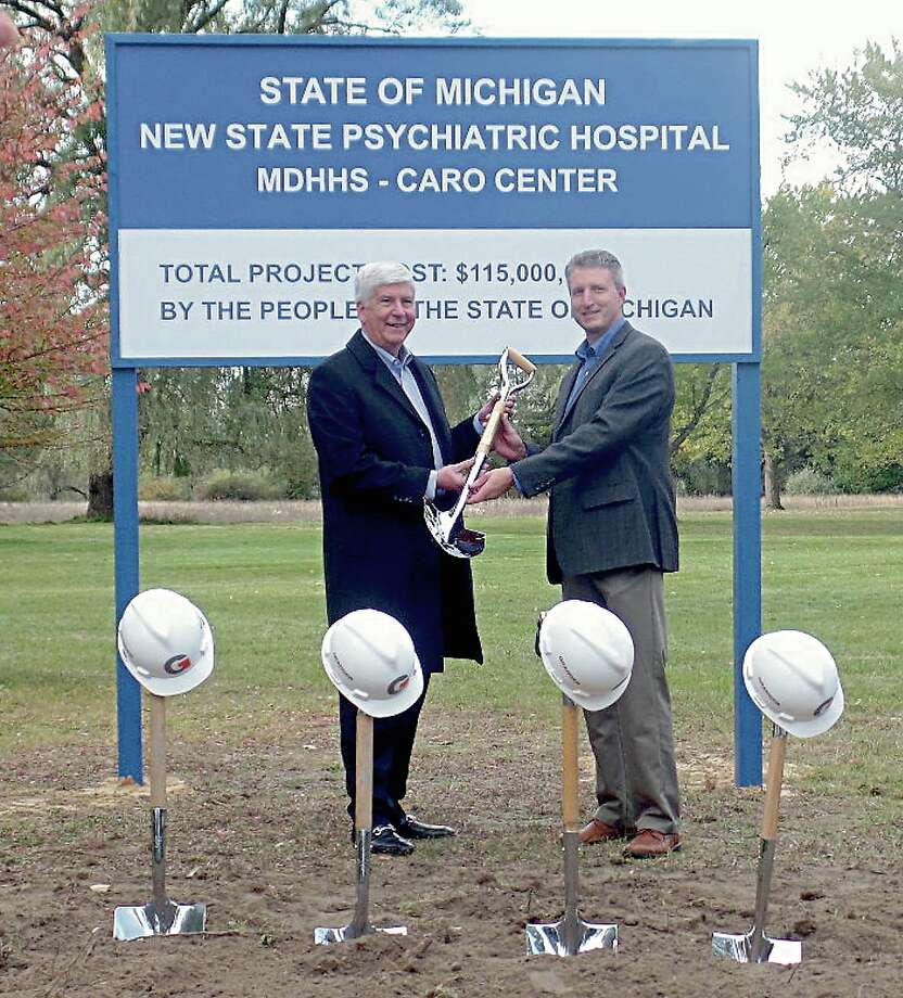 Gov. Rick Snyder, left, hands over a shovel to Granger Construction Company Executive Vice President Dennis Carignan, right, at Friday's groundbreaking for the new $115 million Caro Psychiatric Hospital. Photo: Mary Drier/For The Tribune / Copyright 2012