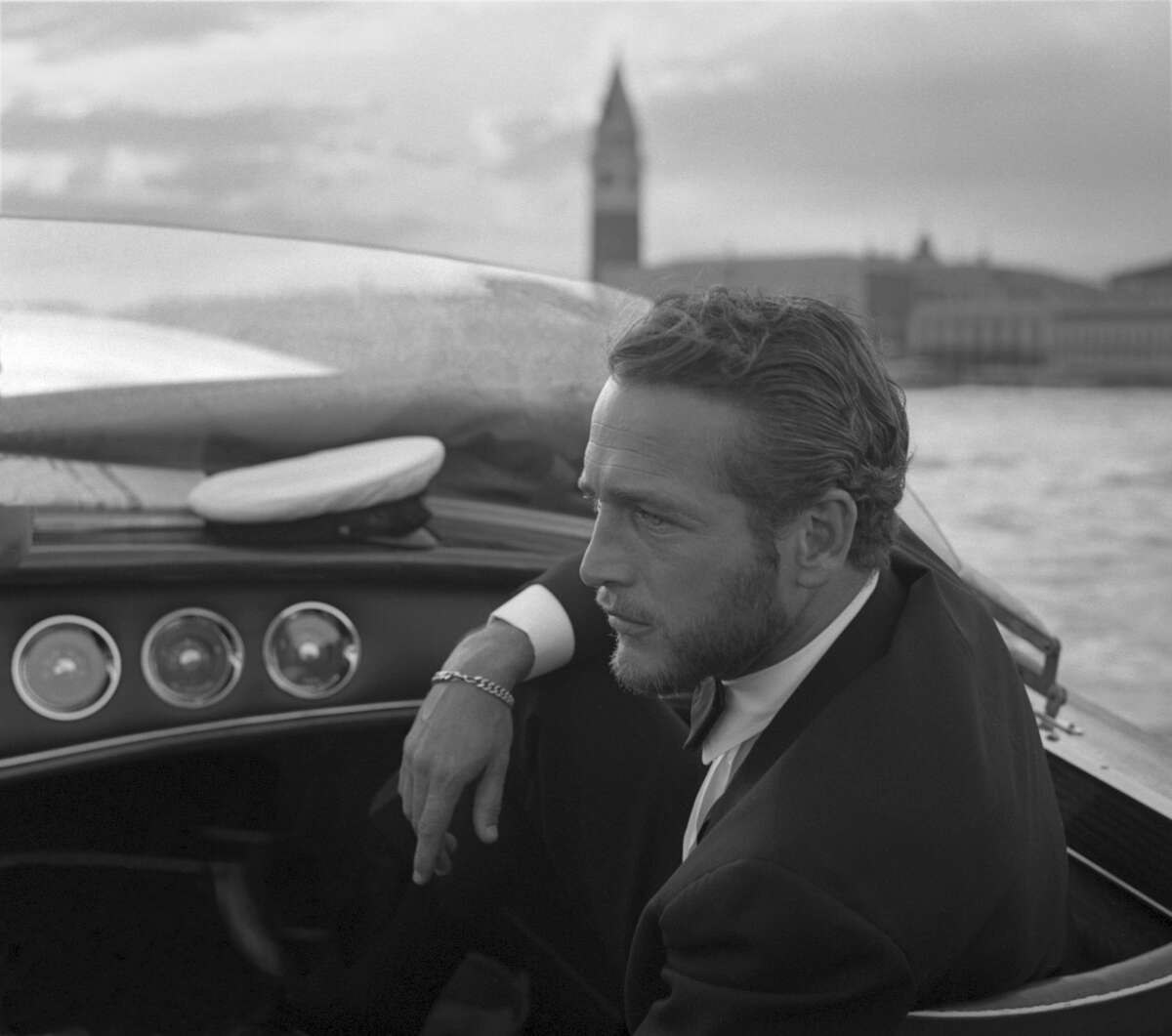 American actor Paul Newman, wearing a tuxedo and a bow tie, portrayed during a trip on a water taxi, a sailor cap on the dashboard, St. Mark Square in the background, Venice 1963. (Photo by Archivio Cameraphoto Epoche/Getty Images)