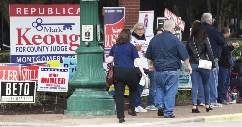 Voters walk past political supporter and rows of campaign signs on their way to cast their ballot on the first day of early voting at the Lee G. Alworth Building, Monday, Oct. 22, 2018, in Conroe. Photo: Jason Fochtman, Houston Chronicle / Staff Photographer / © 2018 Houston Chronicle
