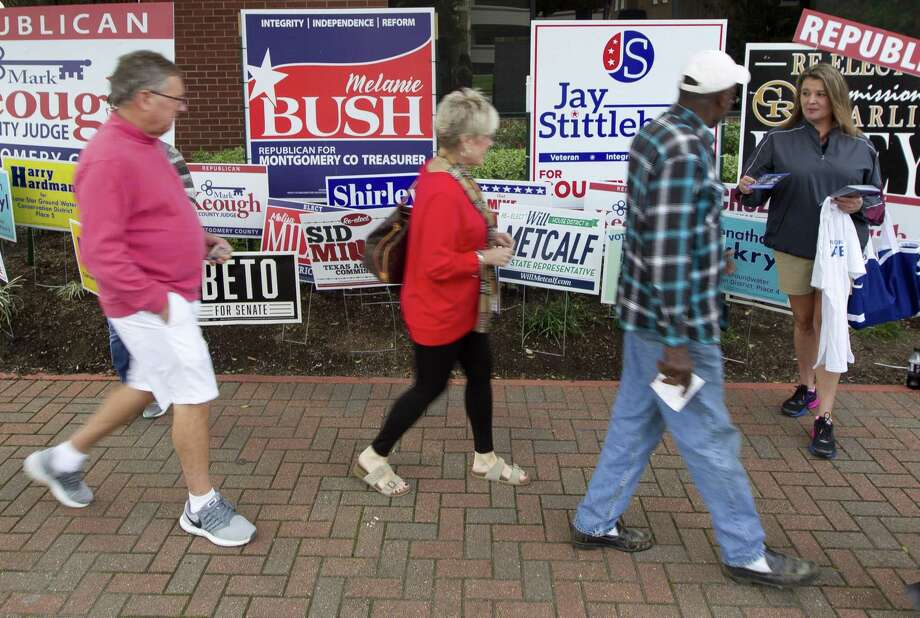 Voters walk past political supporters and rows of campaign signs on their way to cast their ballot on the first day of early voting at the Lee G. Alworth Building, Monday, Oct. 22, 2018, in Conroe. Photo: Jason Fochtman, Houston Chronicle / Staff Photographer / © 2018 Houston Chronicle