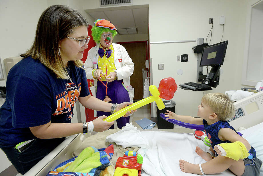 Larry Thompson, aka Dr. U. Getwell, visits with Daina Whittington and her son Dade, 2, as he makes his weekly rounds to patients and staff at Baptist Hospital in Beaumont. Thompson has been volunteering at the hospital since 2007, and calls his clown work a ministry, bringing a moment of joy to patients and families in what is often a difficult time. Friday, October 5, 2018 Kim Brent/The Enterprise Photo: Kim Brent/The Enterprise