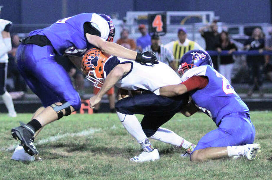Carlinville's Ethan Wallace (right) and Logan Rosentreter (left) combine to sack Pana quarterback Jack Armstrong in the Cavaliers' 49-12 victory in Week 4 at Carlinville. The Cavs capped a 9-0 regular season, their first since 2001, on Friday night with a 66-0 victory over Greenville. Photo: Greg Shashack / The Telegraph