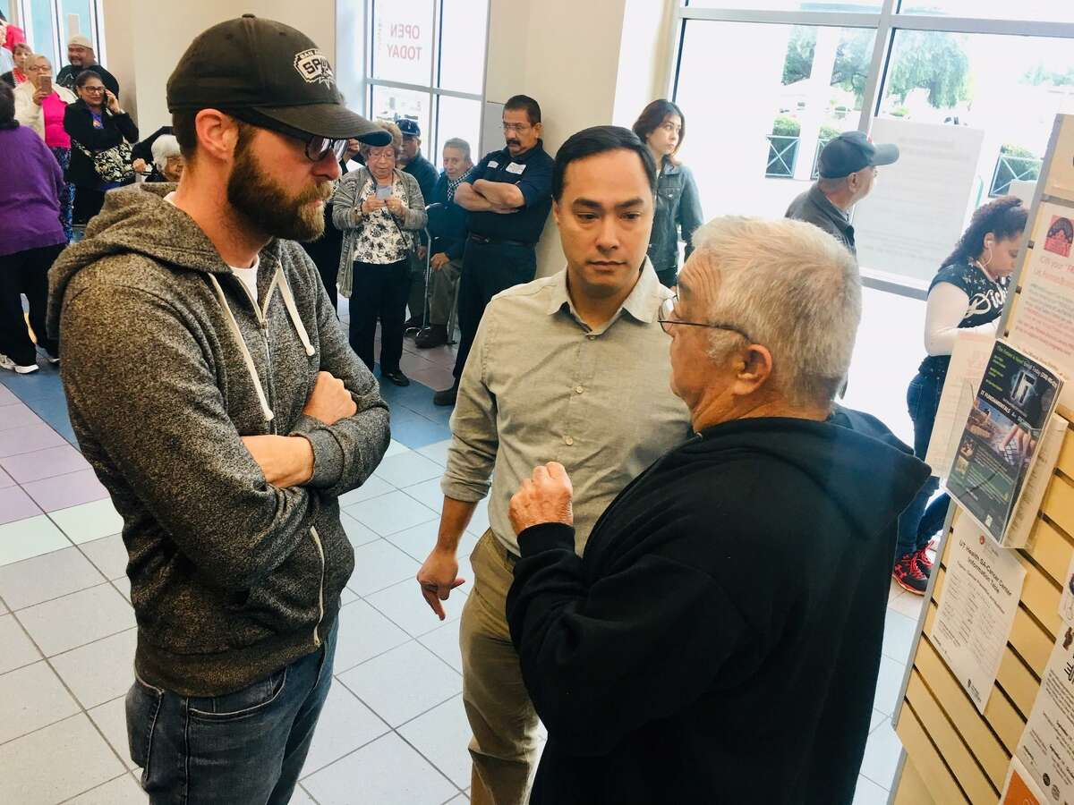 Congressman Joaquin Castro and aide Matt Jones (left) listen to a San Antonio man in line to vote Monday at Las Palmas Public Library on the city's West Side.