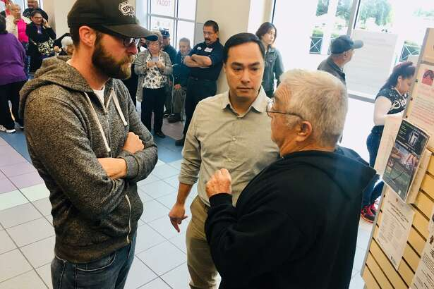 Congressman Joaquin Castro and aide Matt Jones (left) listen to a San Antonio man in line to vote Monday at Las Palmas Public Library on the city's West Side.