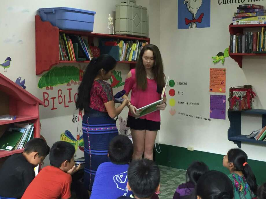 Susan Soh, 17, was named one of the 2018 National Gold Award Girl Scouts for her work to improve literacy rates in Guatemala through creating and stocking an audiobook library in Santa Maria de Jesus. Here, Soh (right) and Teacher Ana Hernandez read to students at SANA clinic, preschool and library in Santa Maria. Photo: Courtesy Photo