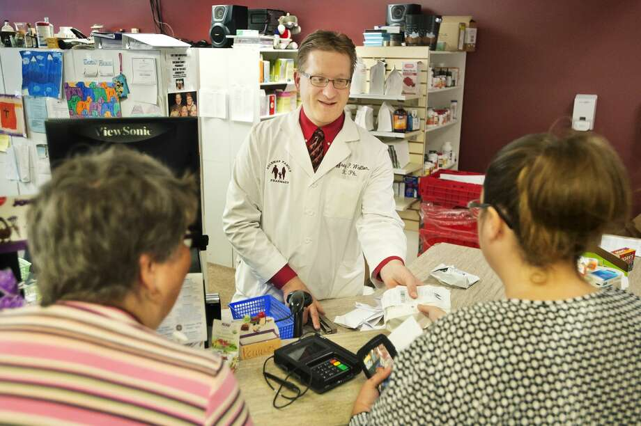 "Coleman Family Pharmacy Owner/Manager Jeffrey P. Walton, R.Ph., center, assists Hope resident Samantha Willett, right, and Danette Zieroff of Sanford, left, inside the pharmacy on Tuesday, Oct. 9, 2018 in downtown Coleman. Willett says she continues to use the pharmacy since she moved out of Coleman because ""they're a great pharmacy."" (Katy Kildee/kkildee@mdn.net) Photo: (Katy Kildee/kkildee@mdn.net)"