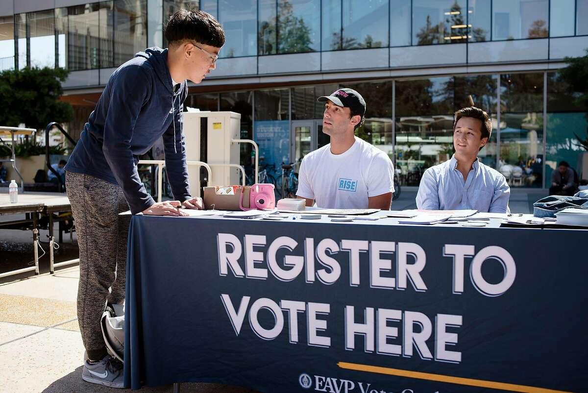 VoteCrew creator and Rise California member Maxwell Lubin, center, and Berkeley City Council candidate Rigel Robinson help Cal student Harry Lee, left, register to vote during a VoteCrew event during National Voter Registration Day on the UC Berkeley campus in Berkeley, Calif., on Tuesday September 25, 2018