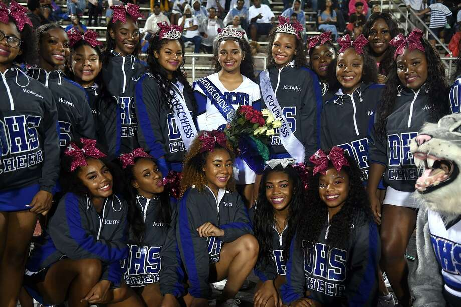 "Angie Tovar, 17, back row center, a senior, after being crowned the 2018 Dekaney High School Homecoming Queen, shares the spotlight with fellow DHS cheerleaders Nila Segobin, 15, left of Tovar, who was crowned sophomore class Duchess, Michelay Rochon, 14, right of Tovar, who was crowned freshman class Countess, and their fellow cheerleaders and school mascot ""Wendy the Wildcat"" after the halftime ceremony at the Wildcat's District 16-6A matchup with Aldine Davis at Leonard George Stadium in Spring on Oct. 19, 2018. Photo: Jerry Baker, Houston Chronicle / Contributor / Houston Chronicle"