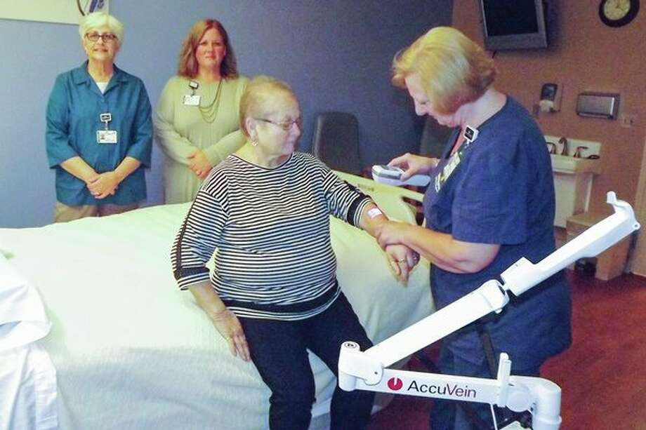Patients receiving infusion services at MidMichigan Medical Center - Gladwin are benefiting from a new piece of equipment called an AccuVein, which is helping with difficult IV starts. Holding the device is Debbie Kruger, R.N., who is demonstrating on volunteer Susan Pahl how the equipment works. Standing in the background is volunteer Lynda Balzer and Julia Reid, R.N., B.S.N., manager, nursing administration. (Photo provided)