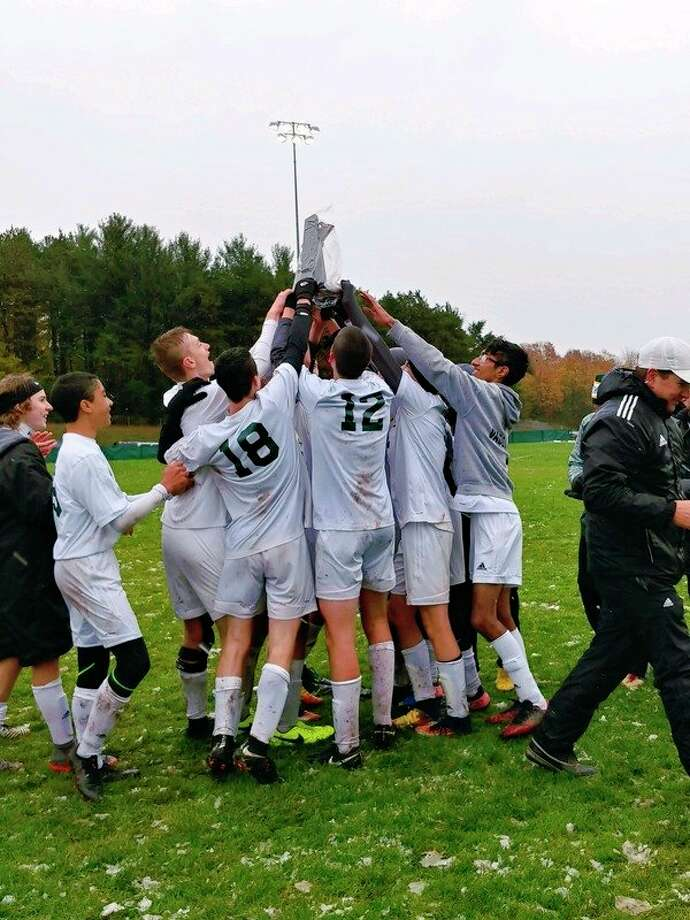 Dow High soccer players lift their district championship trophy in celebration on Saturday after beating Traverse City West 4-3 in the district final in Traverse City. (Photo provided)
