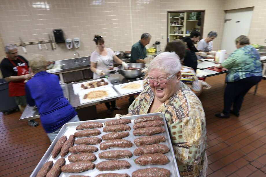 Sue Rizzo carries a tray full of kafta, Lebanese beef kebabs, as volunteers prepare food for the Lebanese Food Festival at St. George Maronite Church in 2014. The three-day festival this year starts Friday at 6 p.m. Photo: JERRY LARA /San Antonio Express-News / © 2014 San Antonio Express-News