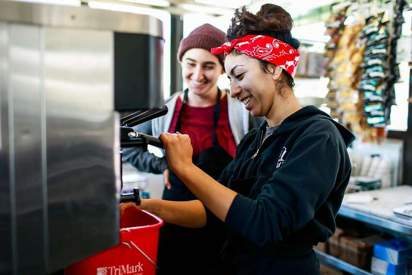 Top: Employee Jason Rose works at the Bi-Rite cafe to get it ready to open at the Civic Center. Above: Natalie Lazard (left) and Kimberly Miramontes test out a machine as they work to get the Bi-Rite cafe up and running three days before the opening.