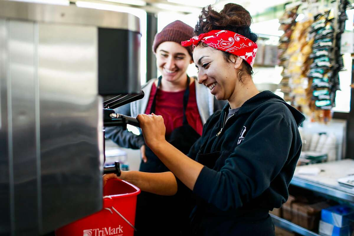 (l-r) Natalie Lazard and Kimberly Miramontes test out a machine as they work to get the Bi-Rite cafe up and running just three days before the cafe opens at Civic Center in San Francisco.