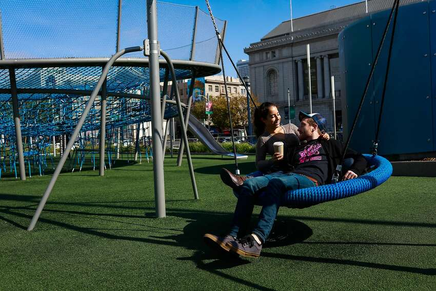 Jessie Cooper and Justin Roth embrace on a swing at a playground at Civic Center.