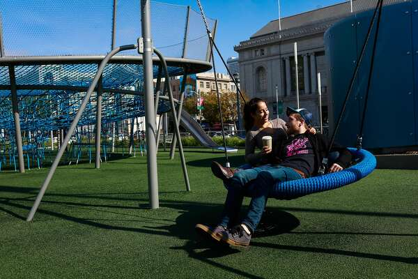 Jessie Cooper and Justin Roth embrace on a swing at a playground at Civic Center in San Francisco, California, on Sunday, Oct. 21, 2018.