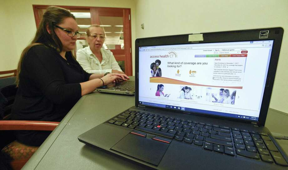 An enrollment specialist with Access Health CT helps enrolls a customer in November 2017 in Stamford, Conn. Photo: Matthew Brown / Hearst Connecticut Media / Stamford Advocate