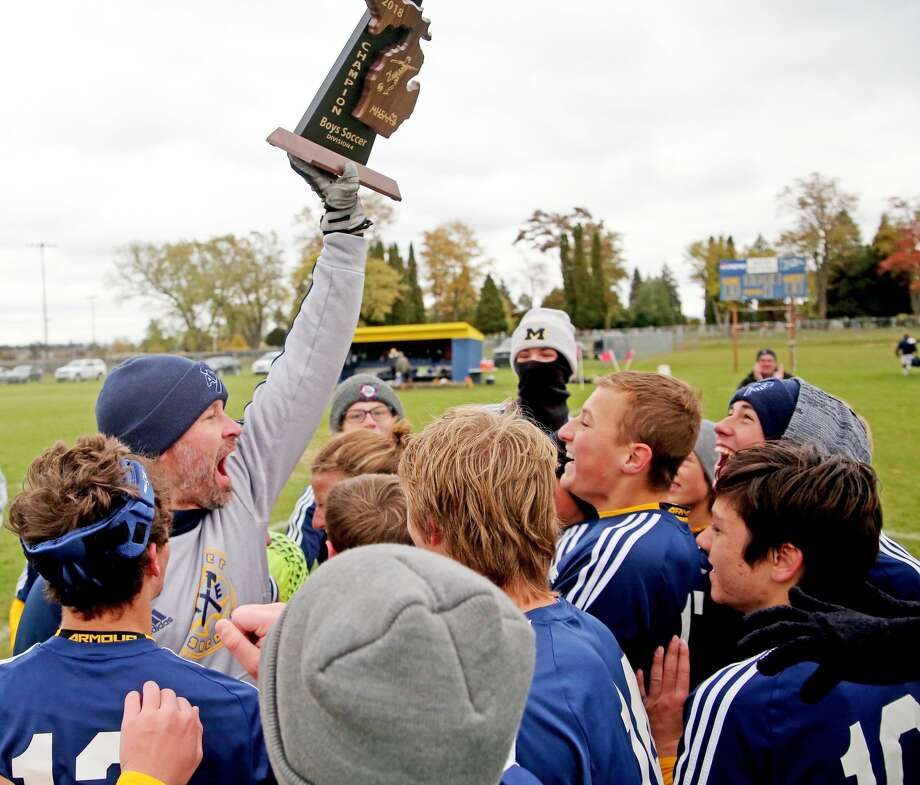 An exuberant Bad Axe soccer coach Adam Sutherland is rushed by his players after the Hatchets captured the Division 4 district soccer championship. They defeated Saginaw Valley Lutheran, 4-2, in the title game, Sunday afternoon. Photo: Paul P. Adams/Huron Daily Tribune