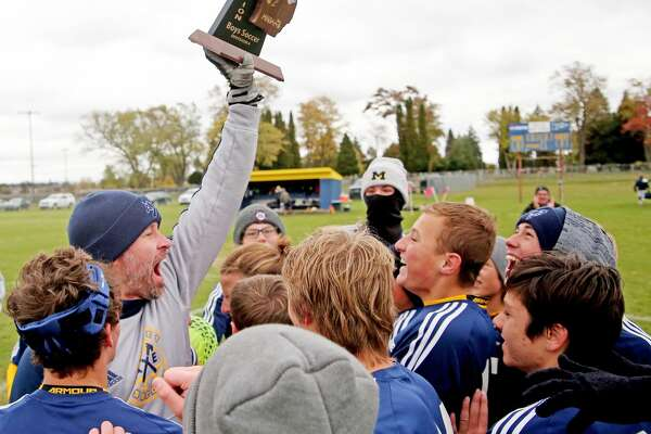 An exuberant Bad Axe soccer coach Adam Sutherland is rushed by his players after the Hatchets captured the Division 4 district soccer championship. They defeated Saginaw Valley Lutheran, 4-2, in the title game, Sunday afternoon.