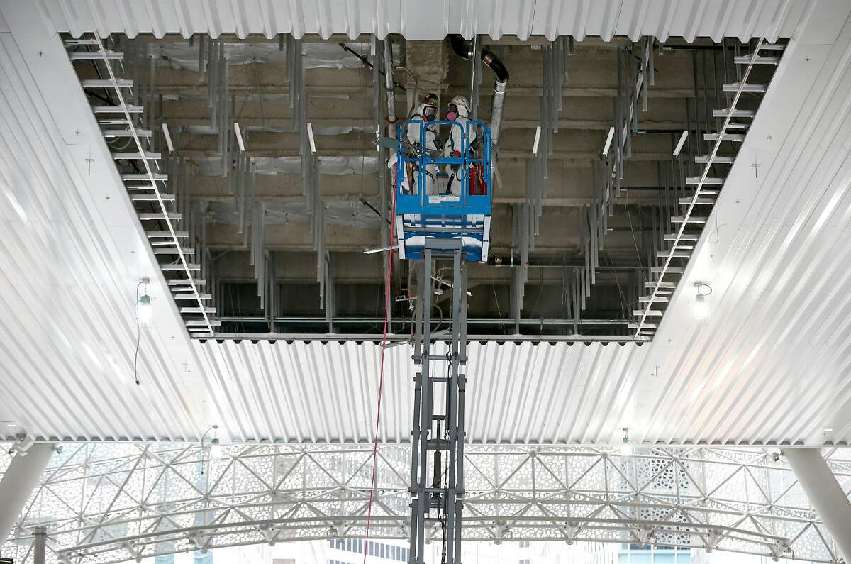 Men in hazmat suits preparing the underside of the Salesforce Transit Center above Fremont Street for a steel beam to be put in place in San Francisco, Calif. on Friday, Sept. 28, 2018. The beam reinforces the structure while work to repair cracks discovered in two other beams can be repaired.