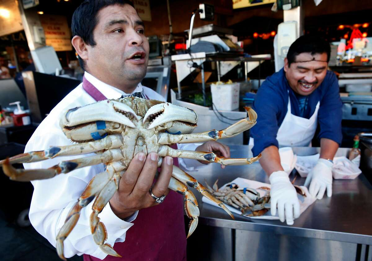 Jorge Cham (left) and Jose Hoil peddle imported Dungeness crabs at Nick's Lighthouse restaurant on Fisherman's Wharf in San Francisco.