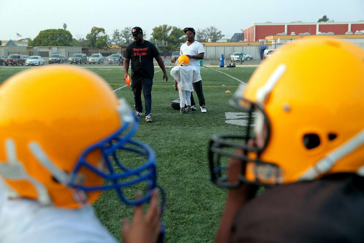Coaches for the six and seven year old teams prepare to have their players do drills during a practice for the Pee -Wee football teams Berkeley Bears and East Bay Panthers at James Madison Middle School in Oakland, Calif., on Thursday, August 23, 2018. The two Pee-Wee teams merged with because of low participation.