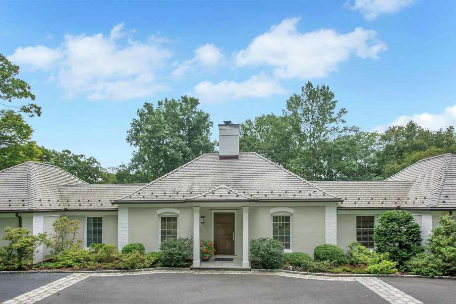The contemporary raised ranch-style house at 113 Brookwood Lane is nestled into a two-acre level and sloping property near the Country Club of New Canaan.