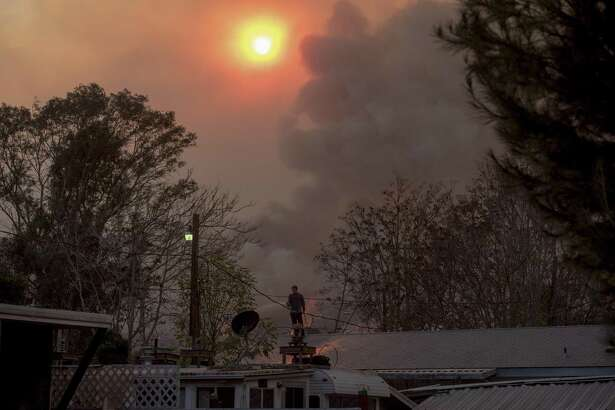 A man sprays down his roof as the Thomas Fire burns on a mountainside in Casitas Springs, Calif., last year. More wildfires is just one consequence of rising temperatures.