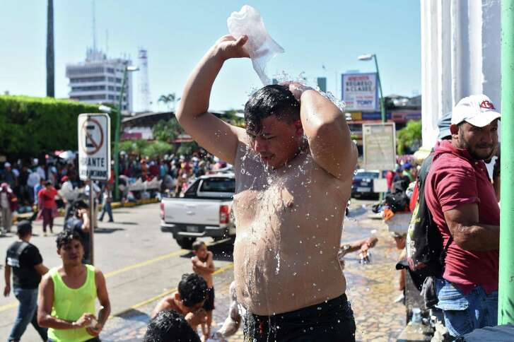A Honduran migrant heading in a caravan to the US, takes an improvised shower in Tapachula, Chiapas state, Mexico, on October 22, 2018. - President Donald Trump on Monday called the migrant caravan heading toward the US-Mexico border a national emergency, saying he has alerted the US border patrol and military. (Photo by Johan ORDONEZ / AFP)JOHAN ORDONEZ/AFP/Getty Images