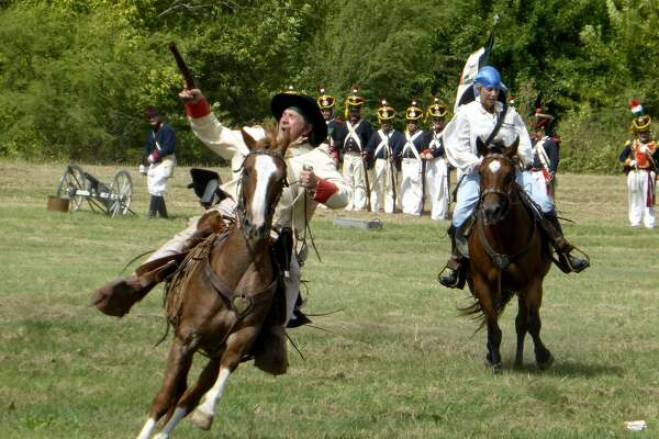 """Soldiers ride past a column of Mexican army troopers as a battle re-enactment begins in last year's """"Texas In Revolt"""" event. This year's re-enactment is scheduled for 10 a.m. to 5 p.m. Saturday in Friendship Park in Kirby,."""