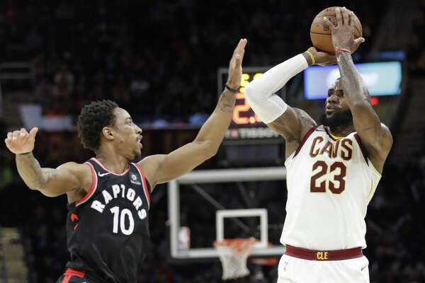 Cleveland Cavaliers' LeBron James (23) shoots over Toronto Raptors' DeMar DeRozan (10) in the first half of an NBA basketball game, Tuesday, April 3, 2018, in Cleveland. (AP Photo/Tony Dejak)