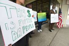 Lead by local activist Hilton Kelley, a small group protesters stand outside Port Arthur's city hall Monday in dissent of the city's recent decision to decline requesting $25,000,000 in Tropical Storm Harvey recovery funds. Photo taken Monday, 10/22/18