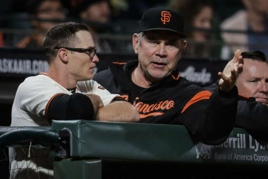 Manager Bruce Bochy chats with Kelby Tomlinson in the dugout during a game. Photo: Gabrielle Lurie / The Chronicle