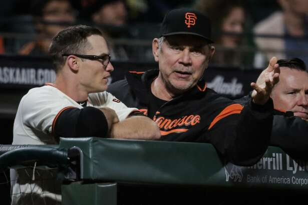 Giants' manager Bruch Bochy (15) (center) chats with player Kelby Tomlinson (37) (left) during a game between the San Francisco Giants and the Milwaukee Brewers at AT&T Park in San Francisco, Calif., on Tuesday, Aug. 22, 2017.
