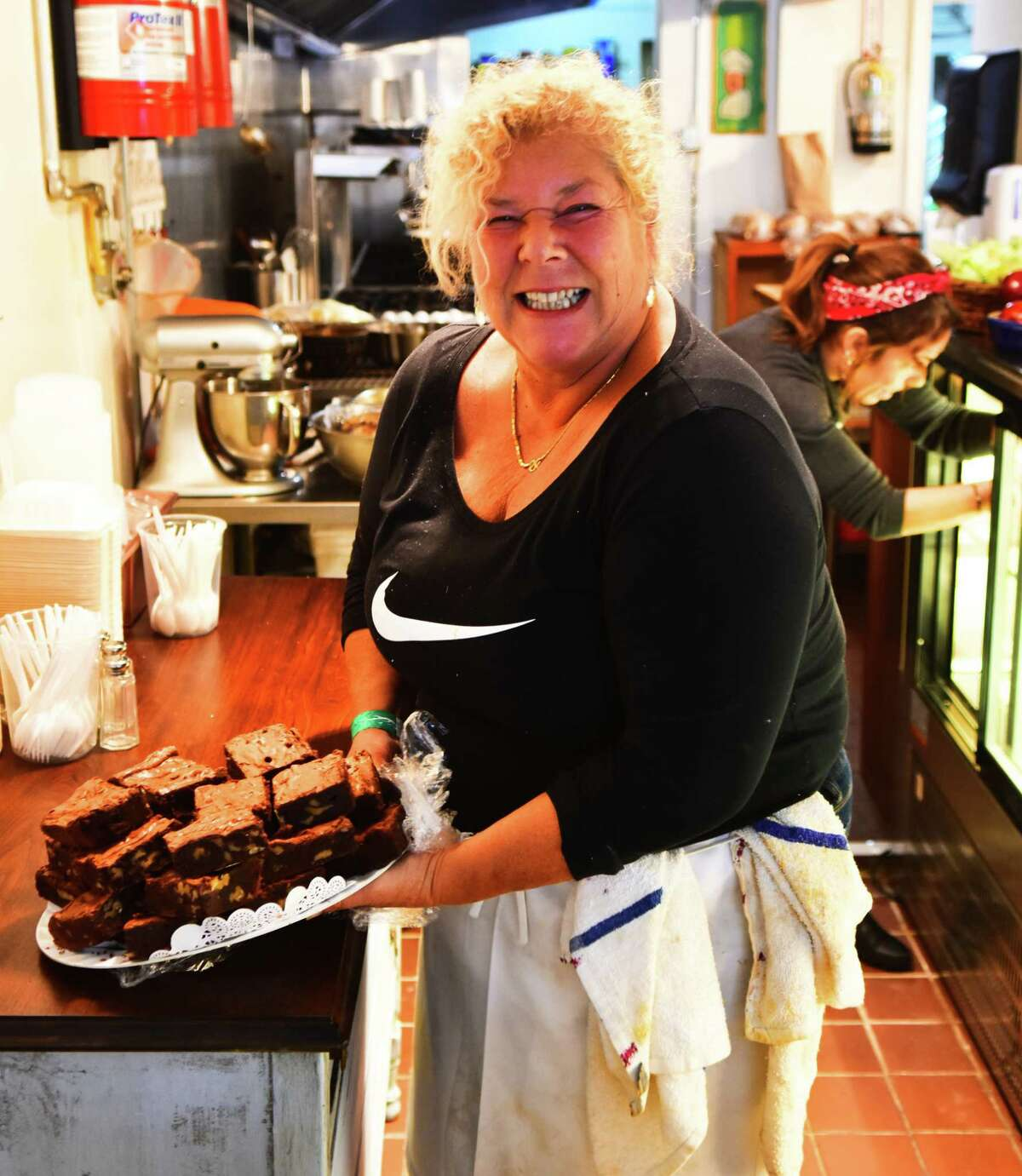 Debbie Klauber with a plate of brownies at Debbie's Kitchen in Albany, which reopened Monday almost nine years after Klauber sold it. (Steve Barnes/.Times Union.)