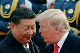 FILE - In this Nov. 9, 2017, file photo, U.S. President Donald Trump, right, chats with Chinese President Xi Jinping during a welcome ceremony at the Great Hall of the People in Beijing. The White House's move to expand Washington's dispute with Beijing beyond trade and technology and into accusations of political meddling have sunk relations between the world's two largest economies to their lowest level since the end of the Cold War.