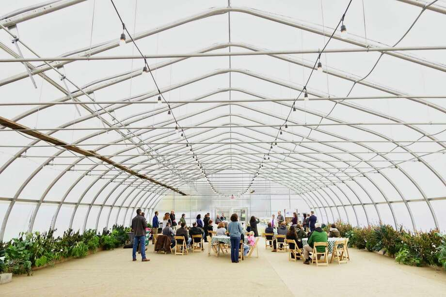 People gather in a greenhouse for a press conference at the Pitney Meadows Community Farm on Monday, Oct. 22, 2018, in Saratoga Springs, N.Y. The press conference was held to announce the Farmland for a New Generation New York program.    (Paul Buckowski/Times Union) Photo: Paul Buckowski / (Paul Buckowski/Times Union)