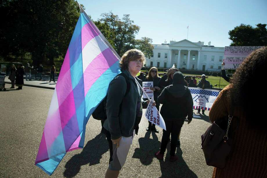 A protester carries a transgender flag outside of the White House in Washington, Oct. 22, 2018. Activists in the LGBT community mobilized a fast and fierce campaign on Monday to say transgender people cannot be expunged from society, in response to an unreleased Trump administration memo that proposes a strict definition of gender based on a person's genitalia at birth. (Sarah Silbiger/The New York Times) Photo: SARAH SILBIGER / NYTNS